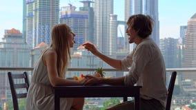 Η νέοι γυναίκα και ο άνδρας έχουν ένα πρόγευμα σε ένα μπαλκόνι αγνοώντας τους ουρανοξύστες του κέντρου πόλεων απόθεμα βίντεο
