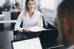 Η νέοι γυναίκα και ο άνδρας συζητούν την εργασία στον πίνακα στην αρχή στοκ εικόνα