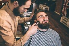 Η Νίκαια και το καλό hairstylist κόβουν μερικές από τη γενειάδα πελατών ` s με ένα ηλεκτρικό razer Κάνει αυτού πολύ Στοκ Εικόνες