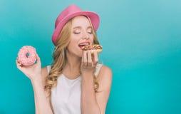 Η Νίκαια και το όμορφο κορίτσι κρατούν ρόδινο doughnut σε ένα χέρι και δαγκώνουν καφετί doughnut ενώ την κρατά με Στοκ Εικόνες
