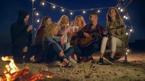 Η νεολαία τραγουδά τα τραγούδια με τα ζεστά ποτά κιθάρων και ποτών από τα πλαστικά γυαλιά καθμένος από την πυρά προσκόπων στην άμ φιλμ μικρού μήκους