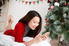 Η νεολαία που χαμογελά την ασιατική γυναίκα χρησιμοποιεί το κινητό τηλέφωνο Χριστούγεννα και Ν Στοκ Εικόνες