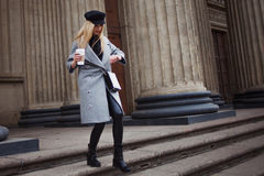 Η νεολαία, το ισχίο και το ελκυστικό ξανθό περπάτημα γύρω από την πόλη με τον καφέ για να πάνε, εξετάζουν το ρολόι και πιέζουν χρ Στοκ φωτογραφίες με δικαίωμα ελεύθερης χρήσης