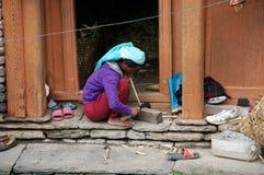 Η νεπαλική γυναίκα κακογράφει μια ράβδο στο κατώφλι του σπιτιού, για την κατασκευή των καλαθιών για τα λαχανικά, στο χωριό του Νε στοκ εικόνα