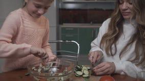 Η νεώτερη αδελφή βοηθά την παλαιότερη αδελφή που η φυτική σαλάτα για τα παλαιότερα αγγούρια φετών κοριτσιών προγευμάτων και νεώτε φιλμ μικρού μήκους