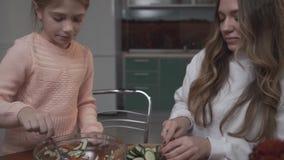 Η νεώτερη αδελφή βοηθά την παλαιότερη αδελφή που η φυτική σαλάτα για τη συνεδρίαση προγευμάτων σε έναν μικρό πίνακα στον άνετο φιλμ μικρού μήκους