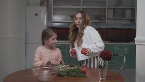 Η νεώτερη αδελφή βοηθά την παλαιότερη αδελφή που η φυτική σαλάτα για τη συνεδρίαση προγευμάτων σε έναν μικρό πίνακα στον άνετο απόθεμα βίντεο