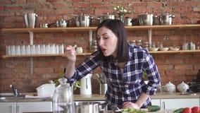 Η νοικοκυρά γυναικών στην προσπάθεια κουζινών χάλασε το πιάτο με ένα κουτάλι από το τηγάνι απόθεμα βίντεο