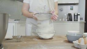 Η νοικοκυρά κοσκινίζει το αλεύρι σε έναν πίνακα απόθεμα βίντεο