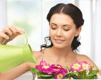 Η νοικοκυρά με το λουλούδι στο δοχείο και το πότισμα μπορούν Στοκ φωτογραφίες με δικαίωμα ελεύθερης χρήσης