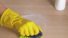 Η νοικοκυρά παραδίδει το λαστιχένιο γάντι σκουπίζει το βρώμικο πίνακα με τον καθαρισμό της σκόνης με τη βούρτσα φιλμ μικρού μήκους