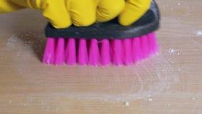 Η νοικοκυρά παραδίδει το λαστιχένιο γάντι σκουπίζει το βρώμικο πίνακα με τον καθαρισμό της σκόνης με τη βούρτσα απόθεμα βίντεο