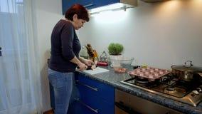Η νοικοκυρά προετοιμάζει το τυρί λουκάνικων ψήνει, λαδώνει τη ζύμη με  φιλμ μικρού μήκους
