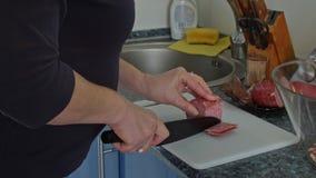 Η νοικοκυρά τεμαχίζει το λουκάνικο γιατί το τυρί λουκάνικων ψήνει απόθεμα βίντεο