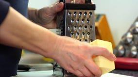 Η νοικοκυρά τρίβει το ξυμένο τυρί τυριών φιλμ μικρού μήκους