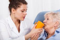 Η νοσοκόμα δίνει την πίνοντας ηλικιωμένη γυναίκα στοκ φωτογραφία με δικαίωμα ελεύθερης χρήσης