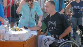 Η νοσοκόμα στα γυαλιά ηλίου μετρά τη πίεση του αίματος ενός ατόμου στην αναπηρική καρέκλα υπαίθρια κατά του πλήθους των ανθρώπων φιλμ μικρού μήκους