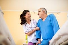 Η νοσοκόμα στη ιδιωτική κλινική βοηθά το ανώτερο άτομο στοκ εικόνα