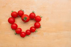 Η ντομάτα κερασιών φρέσκια στη μορφή καρδιών στον ξύλινο τεμαχίζοντας πίνακα, επίπεδο βρέθηκε Στοκ φωτογραφίες με δικαίωμα ελεύθερης χρήσης