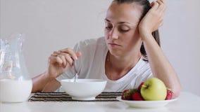 Η νυσταλέα κουρασμένη νέα γυναίκα δεν θέλει να φάει το πρόγευμά της, δημητριακά με το γάλα φιλμ μικρού μήκους
