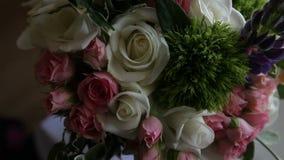 Η νυφική διακόσμηση γαμήλιων ανθοδεσμών των χρωματισμένων λουλουδιών αυξήθηκε στον άσπρο πίνακα φιλμ μικρού μήκους