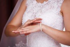 Η νύφη βάζει στο βραχιόλι μαργαριταριών Στοκ Φωτογραφία