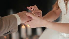 Η νύφη βάζει το γαμήλιο δαχτυλίδι στο δάχτυλο του νεόνυμφου Χέρια γάμου με τα δαχτυλίδια Ο γάμος ανταλλαγής νυφών και νεόνυμφων απόθεμα βίντεο