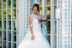 Η νύφη θέτει σε ένα φόρεμα δαντελλών κοντά στα άσπρα stained-glass παράθυρα Makeup των φυσικών τόνων στοκ εικόνες