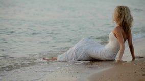 Η νύφη κάθεται στα κύματα άμμου που πλένονται τα πόδια της φιλμ μικρού μήκους