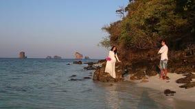 η νύφη κάθεται στο βράχο και ο νεόνυμφος εξετάζει από την παραλία την ανατολή απόθεμα βίντεο