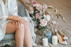 Η νύφη κάθεται το πρωί σε μια εκλεκτής ποιότητας μπλε καρέκλα που ντύνεται σε μια εσθήτα επιδέσμου μεταξιού Στοκ Φωτογραφίες