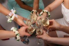 Η νύφη και οι παράνυμφοι κάθονται στα γυαλιά κύκλων και κουδουνίσματος Χέρια με τα βραχιόλια λουλουδιών Στοκ εικόνες με δικαίωμα ελεύθερης χρήσης