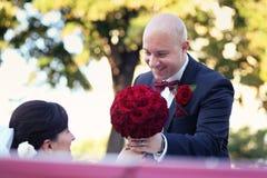 Η νύφη και ο νεόνυμφος έχουν τη διασκέδαση πίσω από τη ρόδα του κόκκινου αναδρομικού εκλεκτής ποιότητας αυτοκινήτου γάμος Στοκ Εικόνες