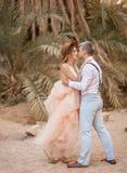 Η νύφη και ο νεόνυμφος αγκαλιάζουν και φιλούν ενάντια στο σκηνικό των φοινίκων Στοκ εικόνα με δικαίωμα ελεύθερης χρήσης