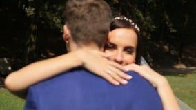 Η νύφη και ο νεόνυμφος αγκαλιάζουν η μια την άλλη σε ένα ηλιόλουστο πάρκο απόθεμα βίντεο