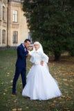 Η νύφη και ο νεόνυμφος αγκαλιάζουν σε έναν περίπατο στην επαρχία για έναν περίπατο Στοκ Φωτογραφία