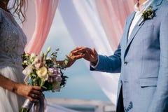 Η νύφη και ο νεόνυμφος ανταλλάσσουν τα γαμήλια δαχτυλίδια Στοκ Φωτογραφίες
