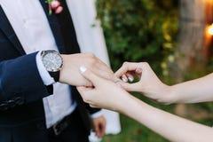 Η νύφη και ο νεόνυμφος ανταλλάσσουν τα δαχτυλίδια κατά τη διάρκεια μιας γαμήλιας τελετής Η νύφη βάζει στον ασημένιο γαμπρό δαχτυλ στοκ φωτογραφίες