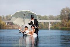 Η νύφη και ο νεόνυμφος είναι ευτυχείς στον ποταμό στοκ φωτογραφία