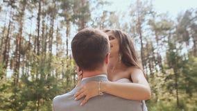 Η νύφη και ο νεόνυμφος θέτουν στο δάσος που ο νέος νεόνυμφος ανυψώνει χαρωπά τη νύφη και την περιβάλλει στις ακτίνες απόθεμα βίντεο