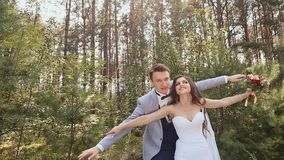 Η νύφη και ο νεόνυμφος θέτουν στο δάσος τα φιλιά και τα αγκαλιάσματα νεόνυμφων η νύφη του Ευτυχής στιγμή ενός αγαπώντας ζεύγους φιλμ μικρού μήκους