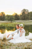 Η νύφη και ο νεόνυμφος κάθονται από τη λίμνη και εξετάζουν το ηλιοβασίλεμα Στοκ Εικόνες