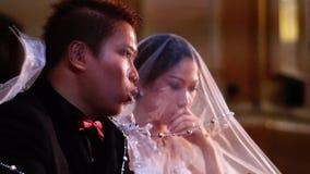 Η νύφη και ο νεόνυμφος κουβεντιάζουν όπως ακούνε τη μάζα κατά τη διάρκεια του καθολικού γάμου στην εκκλησία φιλμ μικρού μήκους