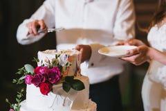 Η νύφη και ο νεόνυμφος κρατούν ένα πιάτο και ένα μαχαίρι και κόβουν το γαμήλιο κέικ με τα λουλούδια και την άσπρη κρέμα Στοκ Εικόνες