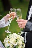 Η νύφη και ο νεόνυμφος κρατούν τα γυαλιά σαμπάνιας Στοκ Εικόνα