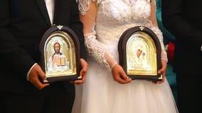 Η νύφη και ο νεόνυμφος κρατούν τα εικονίδια στην εκκλησία κατά τη διάρκεια της γαμήλιας τελετής κλείστε επάνω απόθεμα βίντεο