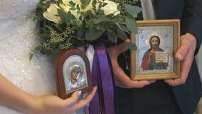 Η νύφη και ο νεόνυμφος κρατούν τα εικονίδια στην εκκλησία απόθεμα βίντεο