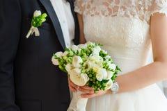 Η νύφη και ο νεόνυμφος κρατούν τη νυφική ανθοδέσμη Στοκ Εικόνες