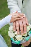Η νύφη και ο νεόνυμφος κρατούν το δαχτυλίδι η νυφική ανθοδέσμη Στοκ Εικόνες