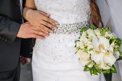 Η νύφη και ο νεόνυμφος κρατούν το δαχτυλίδι η νυφική ανθοδέσμη Στοκ εικόνες με δικαίωμα ελεύθερης χρήσης